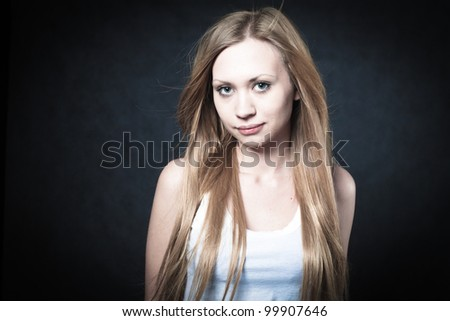 Portrait of a young blond lady on black background - stock photo