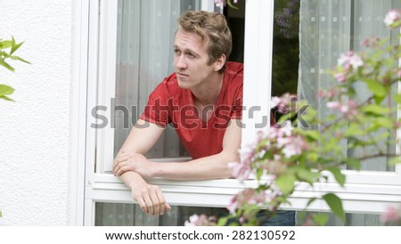 portrait of a young blond man looking out of a window - stock photo