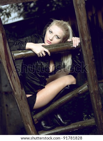 portrait of a young blond sexual woman sitting on the wooden staircase in the abandoned village - stock photo