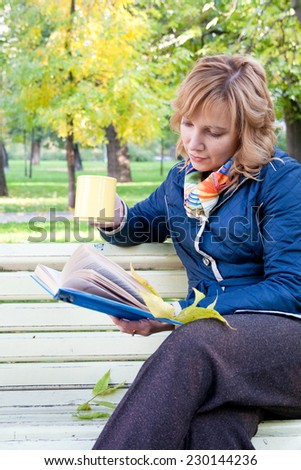 Portrait of a young blond woman reading a book in the autumn park - stock photo
