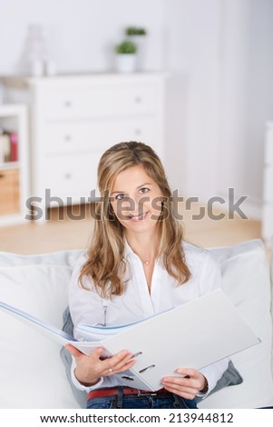 Portrait of a young blond woman with file folder sitting on sofa at home