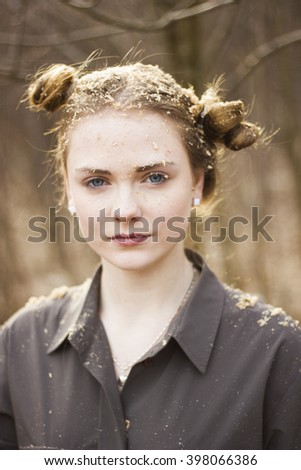 Portrait of a young blonde girl. On hair scattered leaves of the tree. Portrait taken in a forest. Hairstyle Girls are two bun. - stock photo
