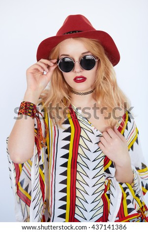 Portrait of a young blonde sensual woman in cow-girl red hat and sunglasses on white background - stock photo