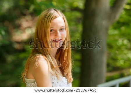 Portrait of a young blonde teen in a forest - stock photo
