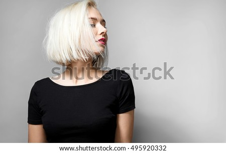 Portrait of a young blonde woman with  red lipstick on her lips in a short black T-shirt