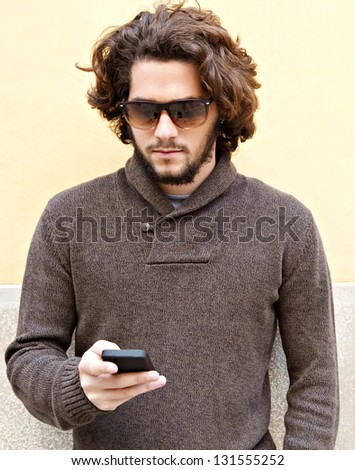 """Portrait of a young bohemian man working on his """"smart phone"""" while leaning on a yellow wall, outdoors. - stock photo"""