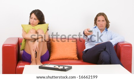 Portrait of a young bored couple sitting on the sofa in their home - stock photo