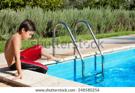 portrait of a young boy by the pool, outdoor - stock photo