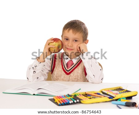 Portrait of a young boy in school at the desk - stock photo