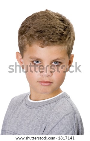 Portrait of a young boy isolated on a white background looking serious.