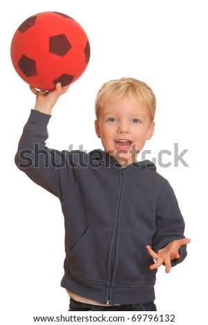 Portrait of a young boy throwing a red ball - stock photo