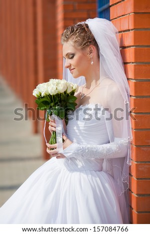 Portrait of a young bride in a white dress with a bouquet of flowers - stock photo