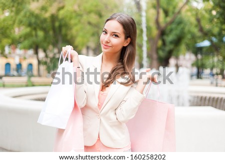 Portrait of a young brunette beauty with shopping bags. - stock photo