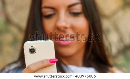 Portrait of a young brunette girl using her mobile phone on park bench. Girl is in blur, while phone is in focus.