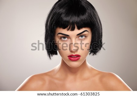 Portrait of a young brunette lady on grey background - stock photo