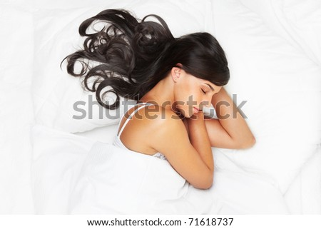 Portrait of a young brunette sleeping in bed - stock photo