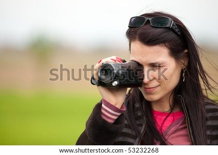 Portrait of a young brunette woman using a camcorder outdoors - stock photo