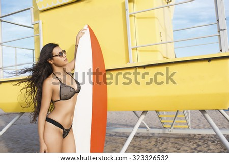 Portrait of a young brunette women in trendy swimsuit standing with surfboard with copy space during her swimming in sunny day, sexy female in bikini sunbathing after surfing during summer weekend - stock photo