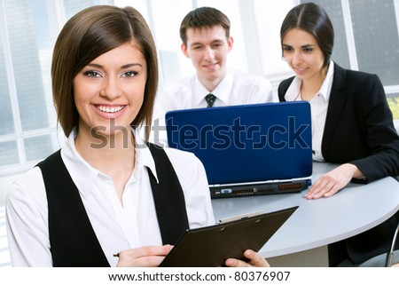 Portrait of a young business lady and her team