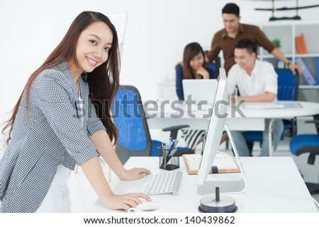 Portrait of a young business lady networking at office on the foreground - stock photo