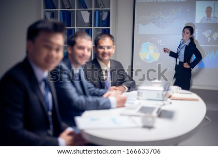 Portrait of a young business lady presenting the company's strategy on the foreground, the colleague is on Skype on the foreground  - stock photo