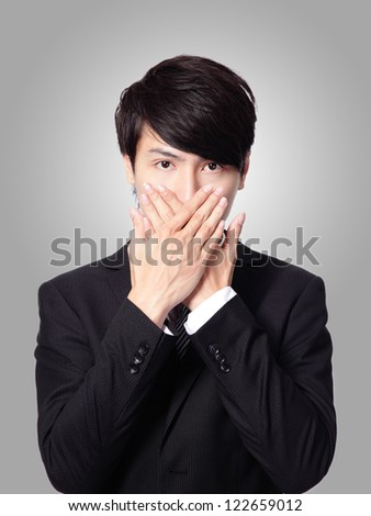 portrait of a young business man covering his mouth with his hand isolated on gray background, asian male model - stock photo