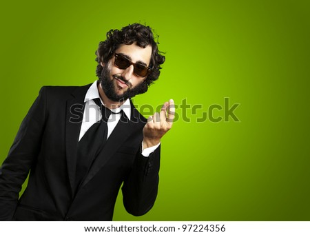 portrait of a young business man gesturing money over a green background - stock photo