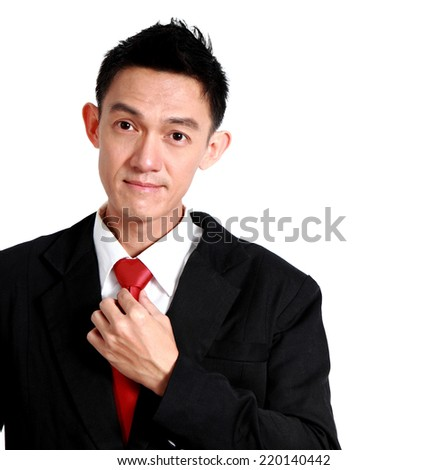 portrait of a young business man looking at the camera while fixing his tie. on a white background.  - stock photo