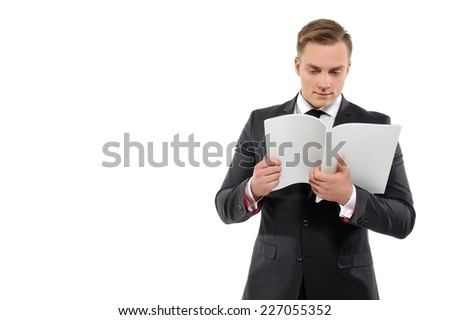 Portrait of a young business man reading journal.Isolated on white background. - stock photo