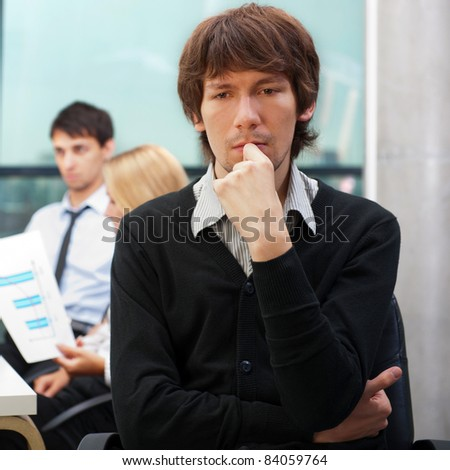 Portrait of a young business man sitting by his laptop in the office with his colleagues at the background - stock photo