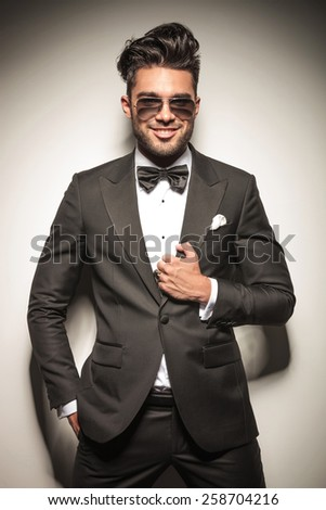 Portrait of a young business man smiling at the camera while fixing his jacket and holding one hand in his pocket. - stock photo