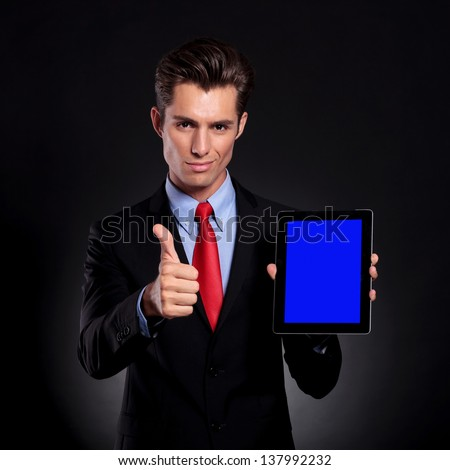 portrait of a young business man standing against a black background presenting a tablet and showing thumbs up sign while smiling to the camera - stock photo