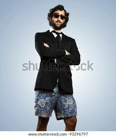 portrait of a young business man wearing a swimsuit against a blue background - stock photo