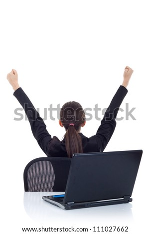 portrait of a young business woman from behind, cheering. Back view of a victorious young business woman in front of laptop. Isolated on white