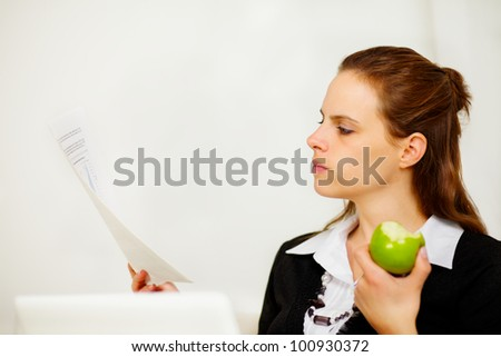 Portrait of a young business woman looking to a document while is eating a green apple - stock photo