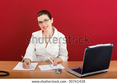 Portrait of a young business woman sitting in office doing some paperwork