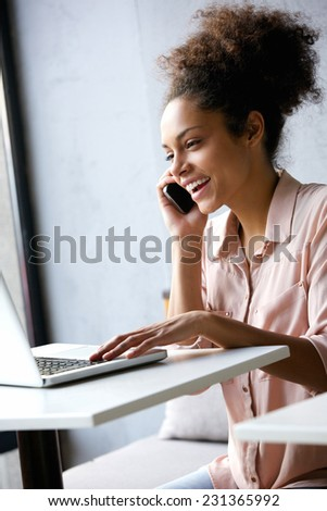 Portrait of a young business woman talking on phone and looking at laptop - stock photo