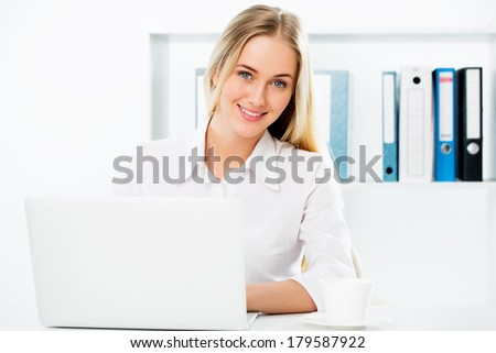 Portrait of a young business woman using laptop at office - stock photo