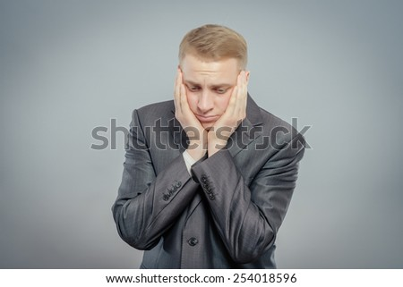 Portrait of a young businessman falls asleep on a gray background - stock photo