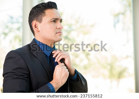Portrait of a young businessman fixing his tie and getting ready for a meeting - stock photo