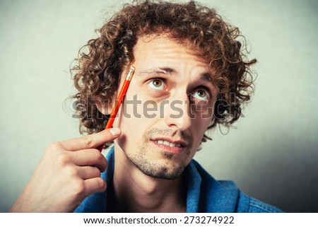 Portrait of a young businessman holding a pencil and thinking. - stock photo