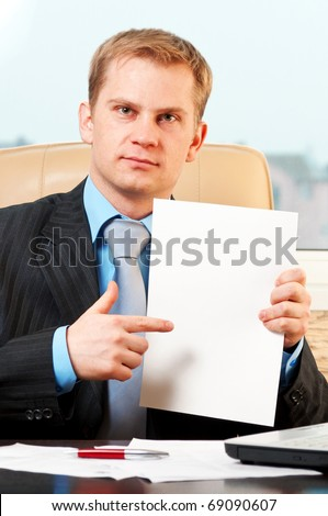 Portrait of a young businessman holding blank paper - stock photo