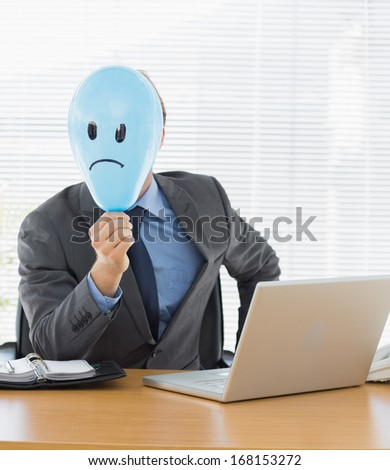 Portrait of a young businessman holding sad smiley faced balloon at office desk - stock photo