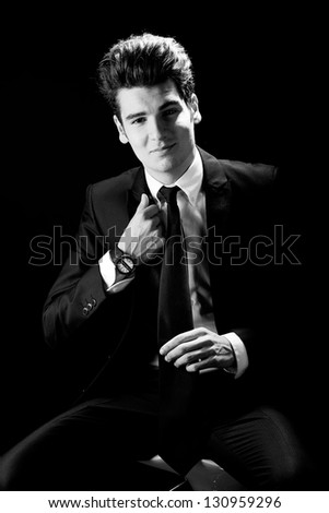 Portrait of a young businessman, isolated on black background - stock photo