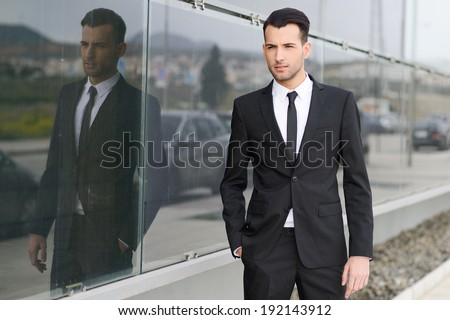 Portrait of a young businessman near a office building wearing black suit and tie with modern haircut
