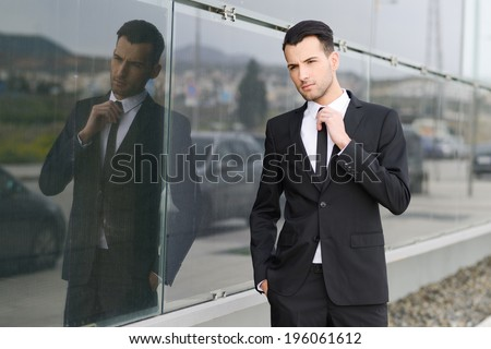 Portrait of a young businessman near a office building wearing black suit and tie with modern haircut - stock photo