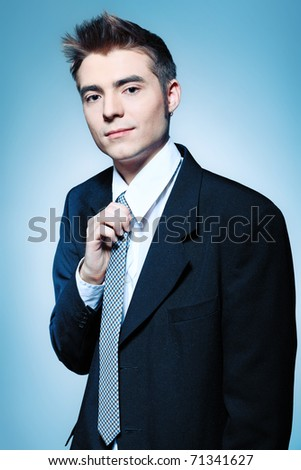 Portrait of a young businessman posing over grey background.
