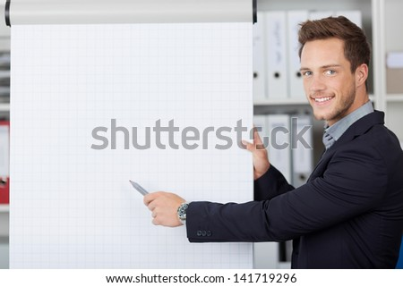 Portrait of a young businessman showing free text space on flipchart - stock photo