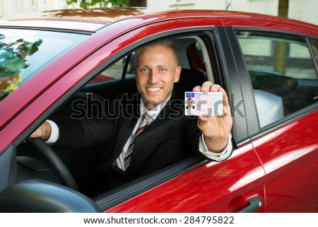 Portrait Of A Young Businessman Showing His Driving License From Open Car Window - stock photo