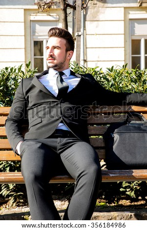 Portrait of a young businessman sitting on a bench